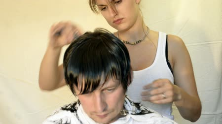 vágás : Hairdresser shears and combs her hair men