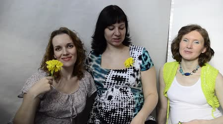 maternidade : Three pregnant woman with yellow flowers in the studio Vídeos