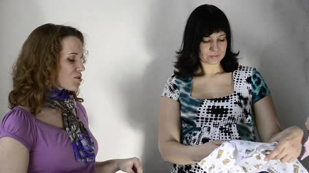 macierzyństwo : Three pregnant women are looking clothes for babies