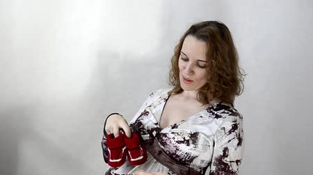 booties : Young pregnant woman playing with baby booties sitting
