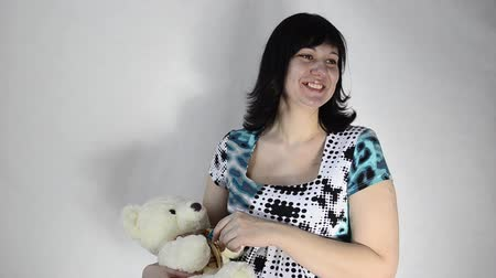 ursinho de pelúcia : Young pregnant woman is playing with a toy bear and a baby pacifier Vídeos