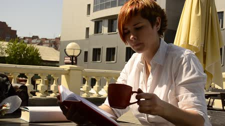 kahve molası : young woman sitting at a table in a cafe, reading a book and drinking coffee Stok Video