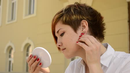 brincos : young woman wears earrings and looks in the mirror Stock Footage