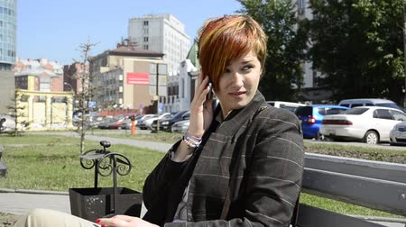 redhead suit : Business Woman talking on the phone on a bench