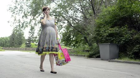 kobieta w ciąży : Young pregnant woman is walking in a park talking on the phone