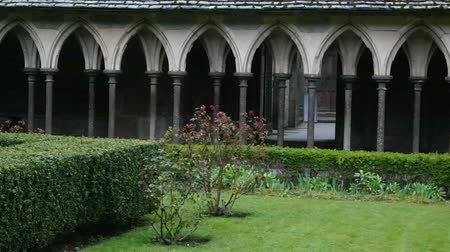 marchs financiers : MONT SAINT-MICHEL, FRANCE - MARCH 27, 2016: Mont Saint-Michel view of the courtyard of the temple with shrubs and flowers