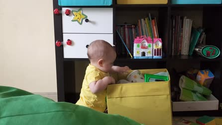 Домашняя жизнь : A small child is playing with toys in a box in the childrens room