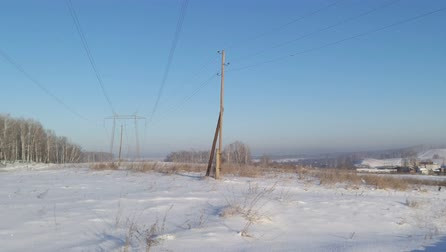 Winter Siberian village on a sunny day in a strong frost. Power line high metal structures