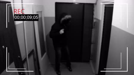 thieve : an armed young man in the mask breaks the door and smashes the security camera and handle a gun Stock Footage