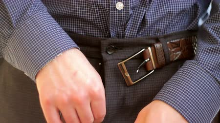 носить : Man in blue shirt buckling undoes the belt on his pants.