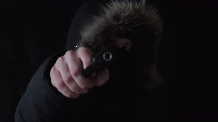 ameaça : the hooded man in a mask threatens with the gun,black background