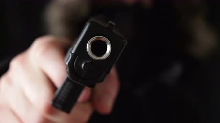 arma de fogo : the young man points the gun at the camera,black background Stock Footage