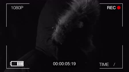 ameaça : the hooded man in a mask threatens with the gun,black background, hidden camera Stock Footage