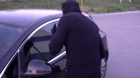 кража : Robber with a crowbar near the car door.