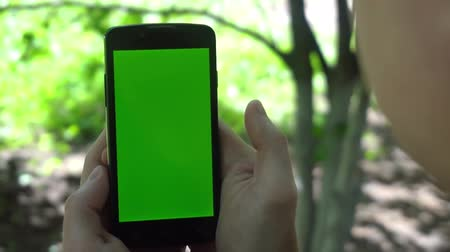 chroma key background : Close-up of male hands touching of smartphone. Green screen Chroma Key. Close up. Tracking motion.