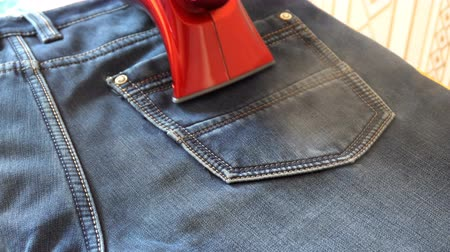crinkle : man steaming denim fabric on ironing table.