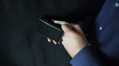 stash : Taking Money Out of a Purse. The man opens a leather purse and pulls out a dollar bill.