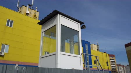 flee : cabin with a loudspeaker on the background of yellow-and-blue buildings and the sky.