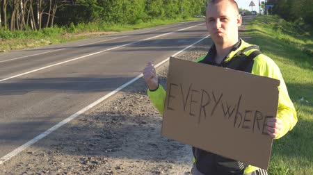 picked up : Hitchhiking traveling young adult man displaying Everywhere written sign board pointing thumb up on interstate highway.