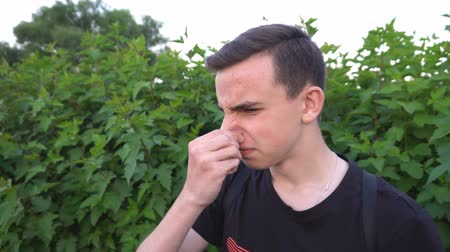 gag : Man gestures a bad smell with his hand, closes his nose with his hands and acts nausea.