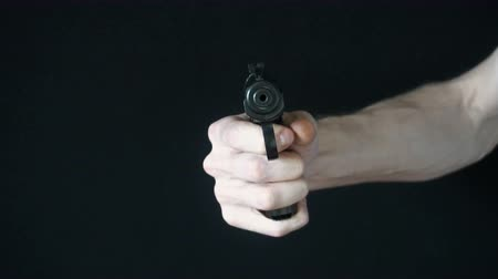 bulletproof : the young man directs at the camera with a black gun and tries to shoot. slow motion. Stock Footage