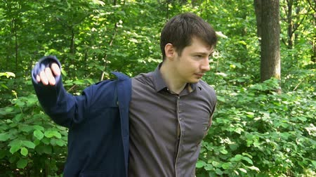 iyi giyimli : young businessman wearing a jacket standing in a forest. slow motion Stok Video