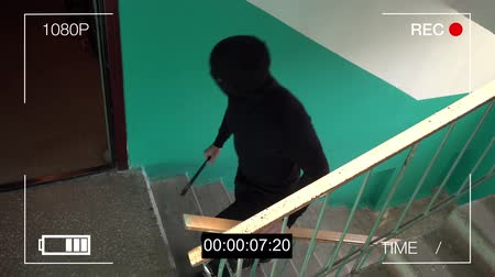 vandalismo : surveillance camera caught the robber in a mask with a crowbar.