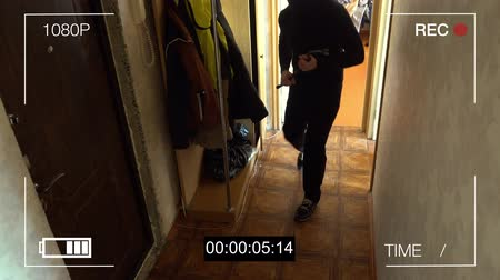 кража : surveillance camera caught the robber in a mask with a crowbar.