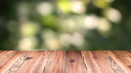 raflar : Perspective wood and bokeh light background. product display template. Wood table top on blur moving natural green leaf background.