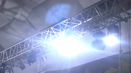 eixo : strobe lights emitting different color beams hanging under the ceiling.
