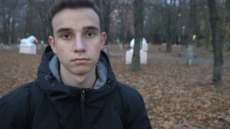 portrait of a serious young man standing in autumn Park. Stock Footage