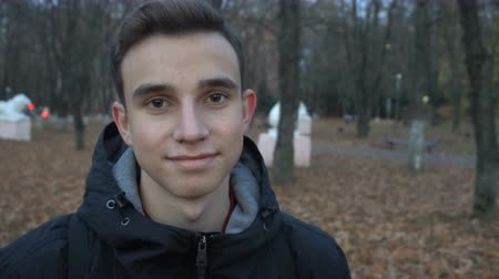 portrait of a smiling young man standing in autumn Park.