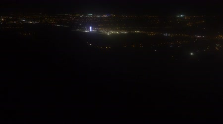 Airplane Window Seat - View of Los Angeles at Night and Wing of Plane on Flight, Traveling in Air over City Lights