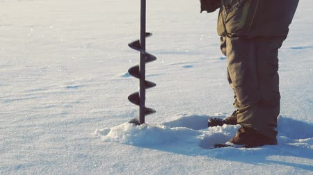 outdoor hobby : drilling through the ice ice fishing
