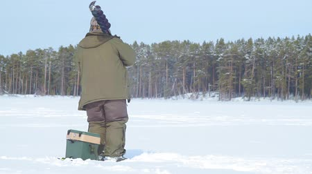 kanadai : fisherman on a frozen lake ice fishing