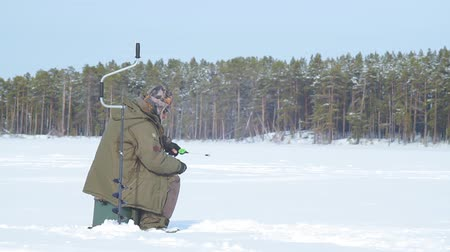 frozen lake : fisherman on a frozen lake ice fishing
