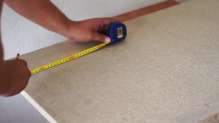 misure : measures the wooden Board with a tape measure