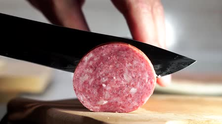 ветчина : cuts sausage with a knife close-up