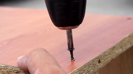винты : twisting the screw into the Board with an electric screwdriver