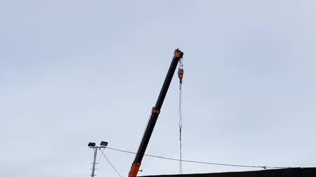 крюк : construction crane lowers the hook on the background of cloudy sky