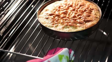tarta de manzana : cooking Apple pie in the oven. Housewife takes the cake out of the oven