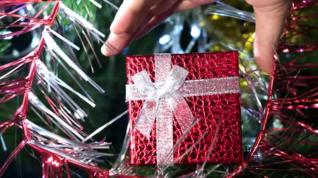 луки : Red gift box closeup for new year and Christmas. Mans hand takes the gift by hand