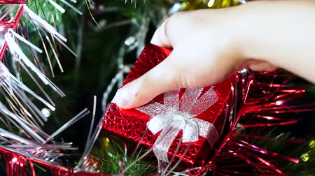 луки : red gift box closeup. a hand takes the gift
