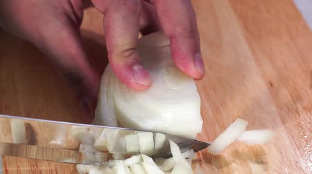 snijplank : Rapidly Chopping Onion, Close-Up. hand cut onions in kitchen. Macro shooting onions. The man cuts onions on a wooden board.