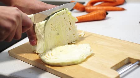 picado : cook slices cabbage on a wooden cutting board. Chopping cabbage with a knife. Stock Footage