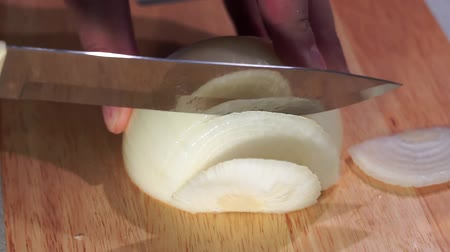 snijplank : man hands is cutting onion on cutting board closeup. Cooking homemade food, slicing vegetables