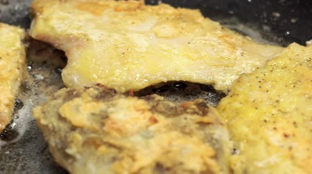 seafood dishes : cooking fried fish in a pan close-up. Breaded flounder fish, fried food