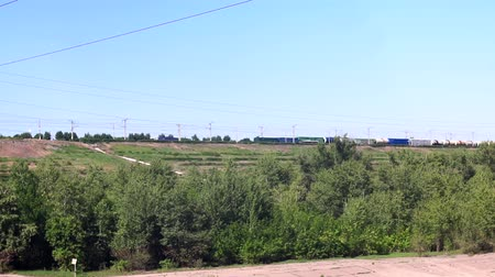 mozdony : long freight train with building materials is moving by railway on the background of fields and forests in the summer on a sunny day. Stock mozgókép