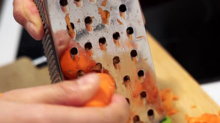 grated carrots on a grater close-up. The concept of cooking food, salads, soups