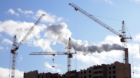 incompleto : Home construction, construction cranes on the background of the plant, the smoke from the chimneys, construction, environmental pollution Stock Footage